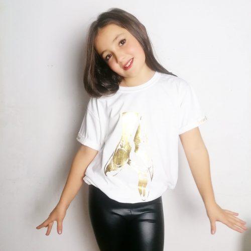 """Les Pointes de ballerine, sont le symbole parfait de la danse Classique Ce t-shirt, simple et élégant, est parfait pour les ados/adultes passionnées de Danse. Ce Top possède des manches courtes à revers. C'est un petit détail, mais sur le revers de chaque manche, se trouve une inscription dorée """"Danse Classique"""". Un élastique à la taille donne un effet blousant à ce Top. Le coté """"dancewear"""" chic et décontracté est alors parfaitement présent. Ce haut, nous transporte dans l'ambiance de noël et dans la féérie du monde de la danse classique!"""