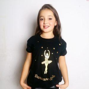 """Le T-shirt fait parti de la collection Danseuse étoile. Le Tutu est le symbole de la danseuse classique. Toutes les petites filles en rêvent! Voici un très joli t-shirt qui pourrait les enchanter ! Le T-shirt possède des manches courtes légèrement ballons. Un élastique à la taille donne un effet blousant à ce Top. Le coté """"dancewear"""" chic et décontracté est alors parfaitement présent. Ce que l'on adore: c'est son dessin en or sur le devant. Tout d'abord on y retrouve une danseuse sur pointes. Elle porte un tutu or pailleté. Elle a la tête dans les étoiles. Puis en bas de scène se trouve l'inscription """"Danseuse Etoile""""."""