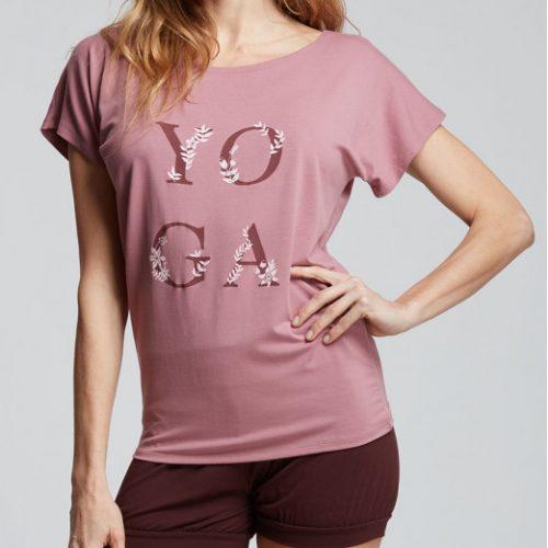 """Ce T-Shirt de Yoga a une coupe loose pour un grand confort . Sur le devant est floqué un logo """"YOGA"""". Ce logo représente le mot YOGA, chaque lettre est entourée de feuilles symbolisant : la posture, la fleur de vie, mais également la connexion à la nature. Avec sa matière très douce et agréable au toucher grâce a ses fils d' origine naturelle végétale, il sera parfait pour faire vos séances de sport . Son encolure dégagée souligne bien le port de tête. Son tissu stretch sera parfait pour une grande liberté de mouvements."""