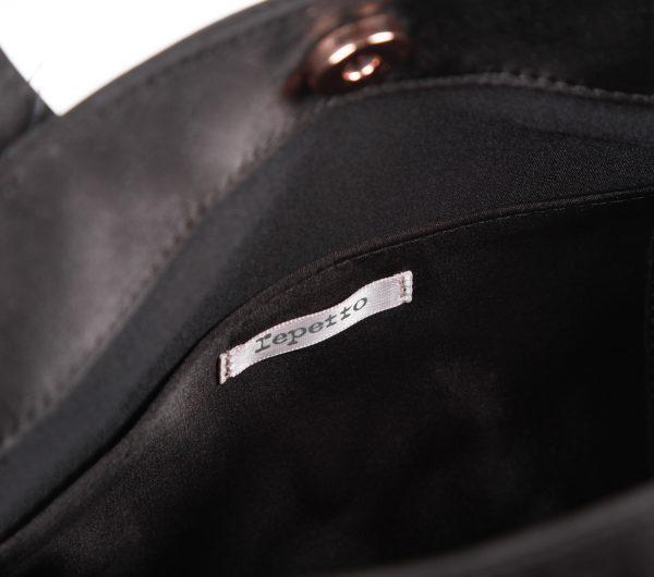 Ce sac à main fantaisie est très féminin. Un modèle plein d'originalité. Les volants sur les côtés du sac rappellent les jupons de danse, tout en apportant une touche d'élégance. En nylon satiné, il sera l'accessoire indispensable pour les fêtes de Noël. Ce petit sac reflète tout l'identité délicate et subtile de la Maison Repetto. Le bouton aimanté de fermeture ainsi que le Logo Repetto sont or rose.