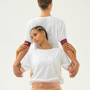 Ce T-shirt coupe droite accompagne parfaitement vos mouvements pendant l'effort ou au quotidien. Ce T-shirt est à manches-courtes, grâce à la bande élastiquée celles-ci on un effet légèrement ballon. Son encolure est arrondie. Grâce à sa taille élastiquée, il se pose parfaitement sur les hanches et dessine une silhouette féminine et sportive. Sur le milieu devant se trouve le logo R. de la maison Repetto.