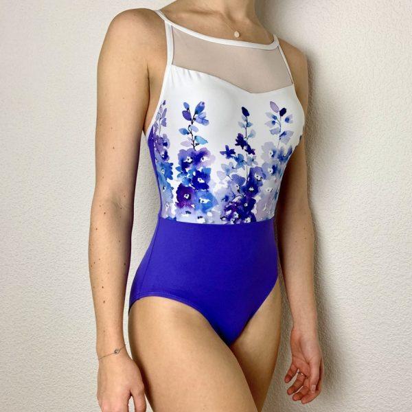 Ce justaucorps à manches bretelles bi-matières fait parti de la collection Jade de la marque Ainsliewear. Il possède une encolure ras cou ronde avec un décolleté en résille. Justaucorps bi-colore avec un imprimé de fleurs violettes et bleues. L'encolure s'arrête au milieu du dos. L'arrière est de couleur violette.