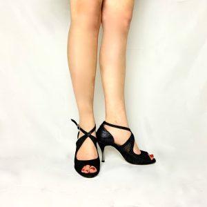 Ces escarpins à talon aiguille sont à bout ouvert en nubuck noir à paillettes. Cette paire, possède des empiècements sur les côtés en résille noire. Celle-ciest ornée de petites paillettes formant des vagues noires. Les empiècements qui se croisent sur le dessus du pied, permettent de bien maintenir le pied, ce qui les rend très confortable.