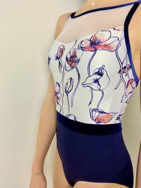 Ce justaucorps à bretelles bi-matières fait parti de la collection Jacq Leo de la marque Ainsliewear. Il possède une encolure ras cou ronde avec un décolleté en résille. Les bretelles ainsi que la ceinture sont en velours bleu marine. Justaucorps bi-colore avec un imprimé de fleurs rose et bleu marine.