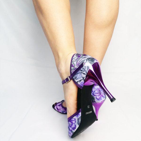 Ses sandalesont une forme simple et élégante. Ce tissu fleurs en camaieu de violet est original et lumineux . La lanière de la cheville, les bords de la sandales ainsi que son talon sont en lurex violet effet métal.