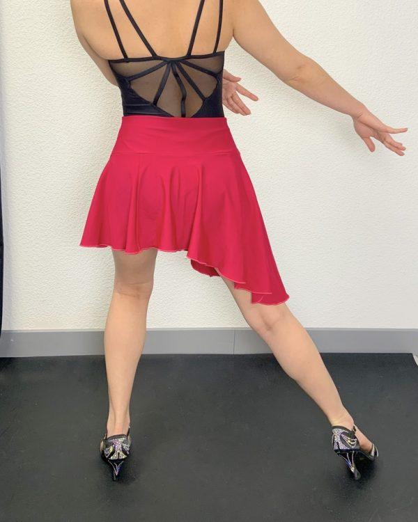 Cette Jupe courte est asymétrique. La jupe est plus longue sur le coté gauche et remonte légèrement sur la droite. Sur le côté droit, se trouve une petite fente avec des volants noirs qui permettent de donner du volume à la jupe lors d'un mouvement.