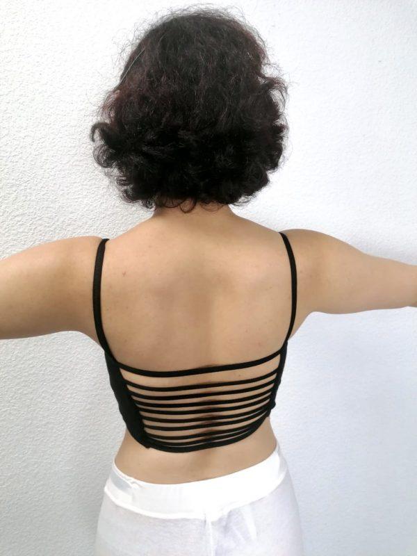 Ce crop top à fines bretelle a une encolure en V. Sur le devant du top, il y a une couture en diagonale afin de mettre en avant le décolleté. Au dos, se trouve des fines bandelettes qui laisse transparêtre la peau. Ce débardeur se prête à tous les sports : fitness, danse, yoga...